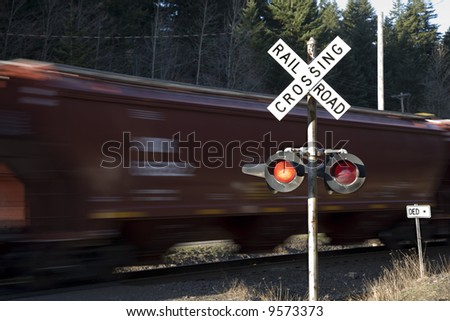 Rail road crossing lights with train in motion - stock photo