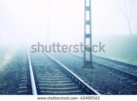 Rail road in morning fog - stock photo