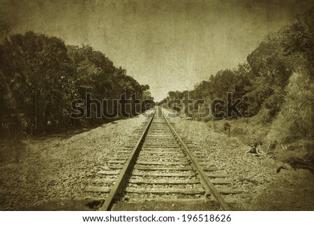 Rail road tracks disappearing into the distance. The photo has had a grunge texture effect applied to make it look old and worn. The photo is in black and white. - stock photo