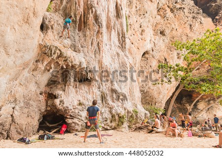 RAILAY, THAILAND - May 4, 2016: Rock climbers climbing the wall on Railay beach, one of the most popular rock climbing locations in Asia.