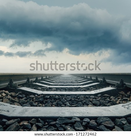 railroad closeup goes to horizon in dramatic sky - stock photo