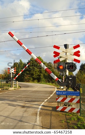 Railroad crossing on a winding road in the dutch countryside where the barriers are closing - stock photo