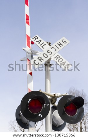 Railroad crossing sign from below with blue sky as a backdrop. - stock photo