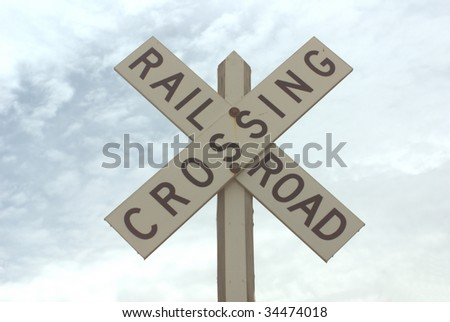 railroad crossing sign with blue sky and clouds - stock photo