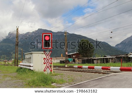 Railroad crossing with a red warning sign in Austrian Alps - stock photo