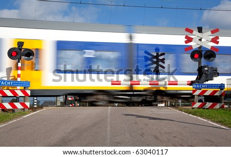 Railroad crossing with high speed train - stock photo