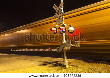 railroad crossing with passing train by night - stock photo