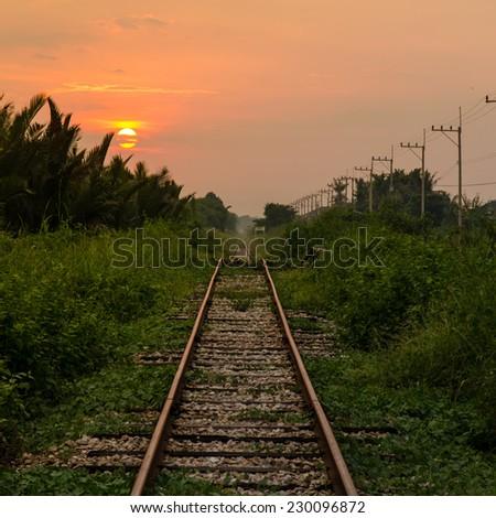 Railroad heading into a sunset, Thailand - stock photo