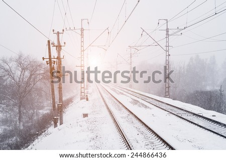 Railroad in winter forest at sunset - stock photo