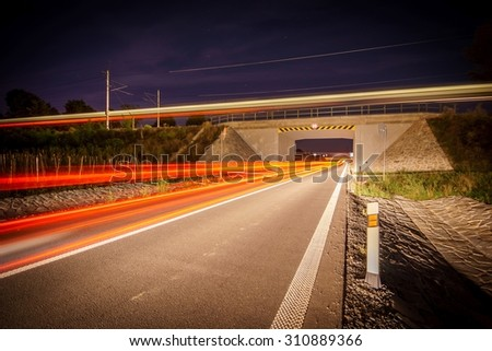 railroad overpass with a passing train and car - stock photo