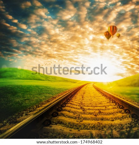 Railroad through the green valley, under blue skies with air balloons - stock photo