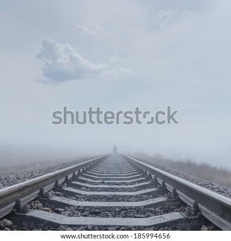 railroad to horizon in fog - stock photo