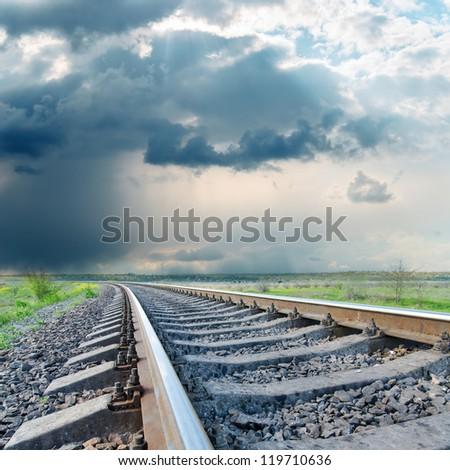 railroad to horizon under dramatic sky. rain before - stock photo