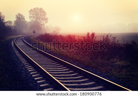 Railroad track during autumn foggy morning in countryside - stock photo