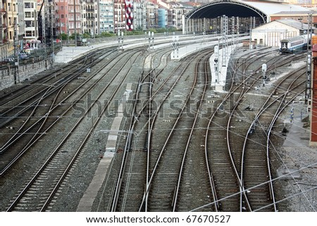 Railroad tracks and catenary, with crossings of roads and sidewalks. Bilbao, Euskadi, Spain. - stock photo