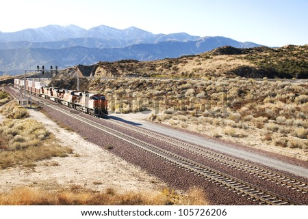 Railroad tracks and train in the American desert - stock photo