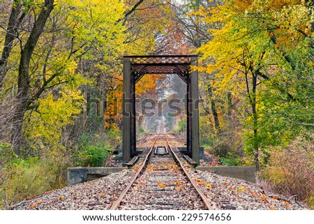 Railroad tracks cross a trestle surrounded by trees with colorful fall foliage. - stock photo