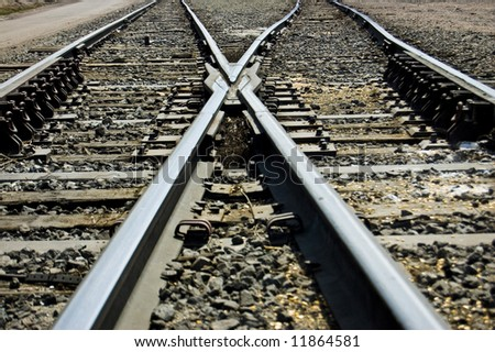 Railroad tracks cross. Interesting X shape. - stock photo