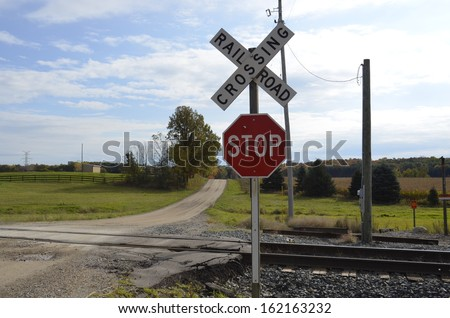Railroad Tracks crossing a dusty dirt road in rural Michigan, USA - stock photo