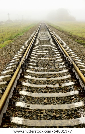 Railroad tracks in foggy weather, the autumn period - stock photo