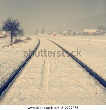 Railroad tracks in winter landscape presented in retro style; shallow focus depth and natural fog create dreamy feeling; filters also applied for vintage effect. - stock photo