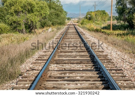 railroad tracks leading to distant foothills of Rocky Mountains in northern Colorado - stock photo
