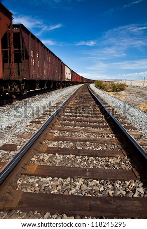 Railroad Tracks with Train Curving into the Distance
