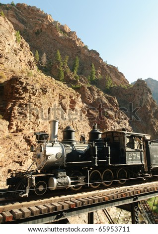 railroad train on a steel bridge through the Black Canyon - stock photo