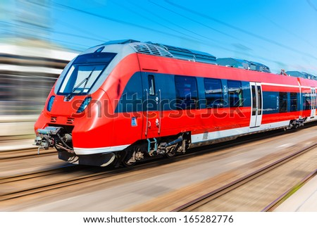 Railroad travel and railway tourism transportation industrial concept: scenic summer view of modern high speed passenger commuter train on tracks with motion blur effect - stock photo
