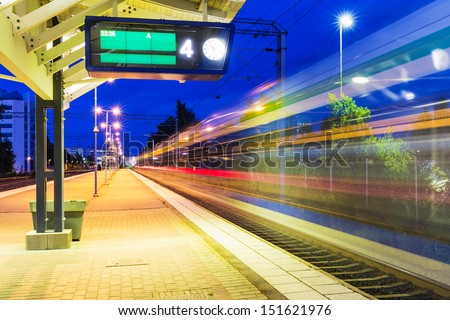 Railroad travel and transportation industry business concept: summer night view of high speed passenger train departing from railway station platform with motion blur effect - stock photo