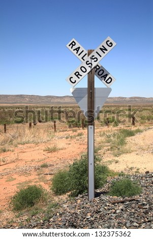 Railroad warning crossing sign on a rocky base in a desert landscape.