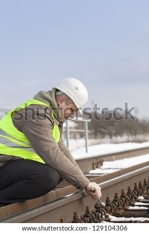 Railroad worker with adjustable wrench fix the nut - stock photo