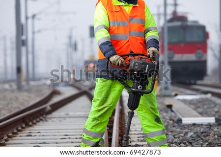 rails are getting repaired by a worker and his machine - stock photo