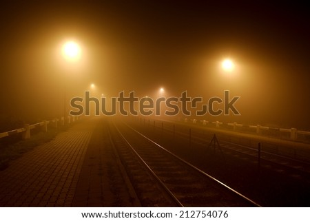 Rails in the fog at night - stock photo
