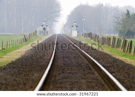 Railtrack with hazy crossing in the background. - stock photo