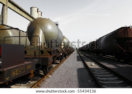 Railway and rusty wagons and grey sky above