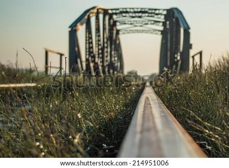 Railway bridge in morning sun - stock photo