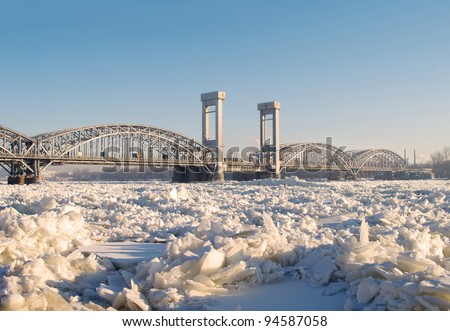 Railway bridge on the frozen river Neva in sunny day - stock photo