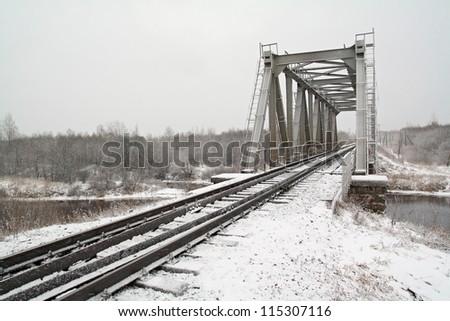 railway bridge through small river - stock photo