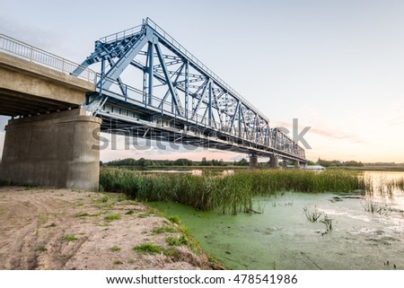 railway bridge with metal rails near river in sunset