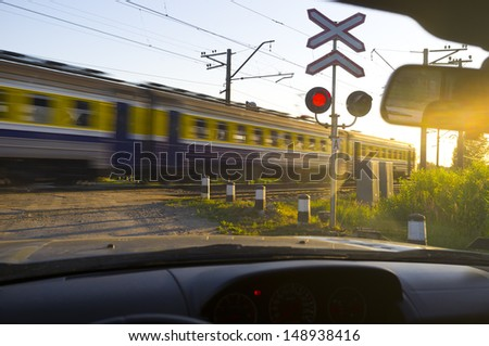 railway crossing in sunset with train passing - stock photo