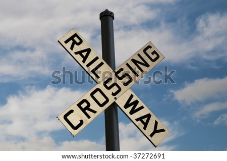 Railway Crossing sign with bright blue sky behind it - stock photo