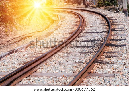 Railway curve in forest at sunset time. - stock photo
