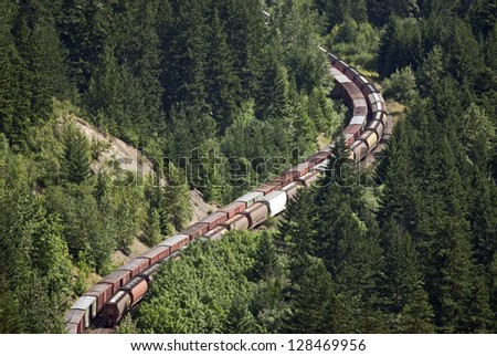 Railway line - long freight trains with tankers and containers runs through curves in the mountain forest, (Fraser Canyon), British Columbia, Canada - stock photo