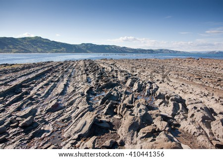 railway line undersea rock formations, Tatapouri reef near Gisborne, East Coast, North Island, New Zealand, low tide on a blue, sunny Autumn day    - stock photo