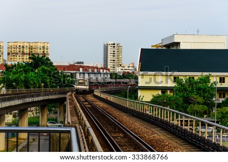 Railway lines/tracks of electric subways surrounded by public housing apartments at sunset in Singapore. Transportation and urban concept - stock photo