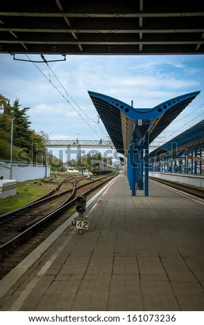 Railway platform and rails at the railway station without passengers and trains. Urban landscape - perspective way on a railroad. Crossing railroad tracks and blue signal lamp on a railway junction. - stock photo