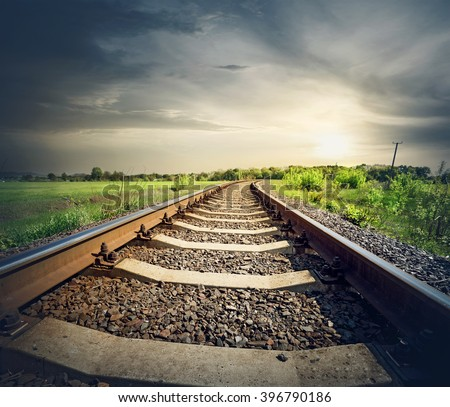 Railway stretches to the sun in the field