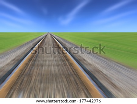 Railway track blurred, green grass and blue sky on the horizon - stock photo