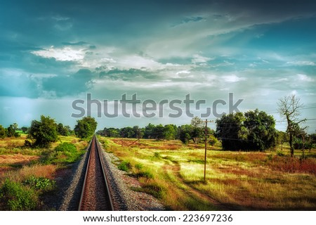 Railway track crossing rural landscape under evening sunset sky. Travel concept in vintage hipster style